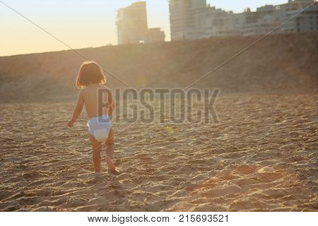 Rear View Of Running Child On Seaside In Beautiful Sunset
