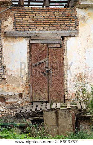 Old wooden abandoned door and brick wall