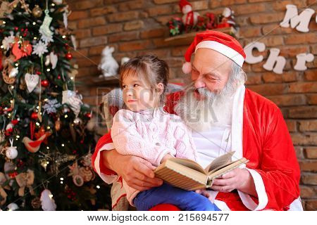 Inquisitive female child listens attentively to interesting story from book read by Santa Claus in cozy and spacious room decorated for New Years holidays with large floor lamp, walls on which Christmas posters hang, high bright tree under gifts lie boxes