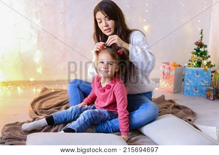 Beautiful girl and elder sister of small female child cares for younger sister and talks, hugs and braids up hair on head, fools around and laughs cute in family way, sitting on floor in bright room against backdrop of glowing garland and small festive tr