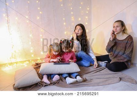 Two elder sister girls together with little girls younger sister spend time and talk with four of them, young women discuss affairs and gossip, talk on phone and watch children, two little girls play games on tablet, sit on floor in a bright room on backg