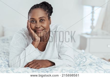 Content young African woman wearing pajamas lying on her bed with her hand on her chin while waking up in the morning
