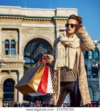 Rediscovering things everybody love in Milan. Full length portrait of modern traveller woman with shopping bags in Milan Italy looking into the distance