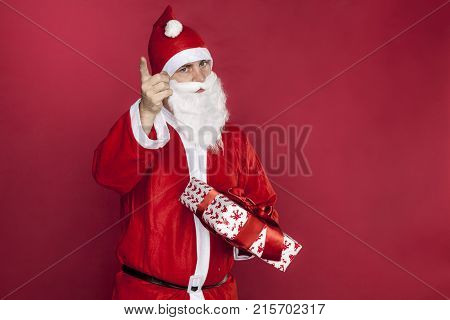 Santa Claus Is Holding A Gift And Threatening His Finger