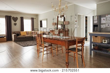 Interior of a contemporary suburban home decorated with country style dining table with a modern sofa in the living room