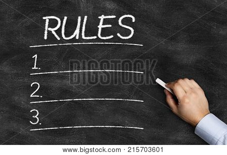 Rules List written on the blackboard with hand holding white chalk