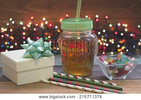 A festive still life with a glass clear cup of tea with a green plastick cap and a straw, a bowl of colored candies, a light giftbox with a sh