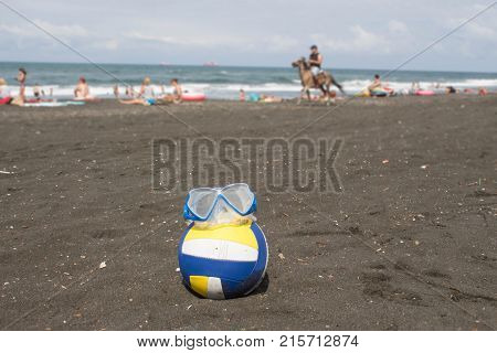 Ball and swimming glasses on beach. Blurred photo of people on sand beach. Travel or sea vacations concept. Beach life