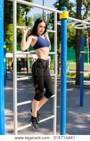Young female in a bright blue sport bra and black leggings leaning against the horizontal bar on the sport playground. Photo of an athlete girl with a beautiful sports body