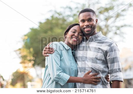 Smiling young African couple standing arm in arm together while enjoying a sunny day outside