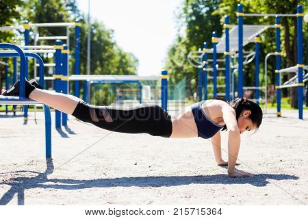 Young sportive girl in a bright blue sport bra and black leggings doing push ups on the sport playground. Photo of an athlete girl with a beautiful sports body