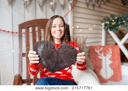 Christmas or New Year celebration. Happy woman sitting in the rocking chair. Holding a heart figure out of wood. selective focus and copy space.