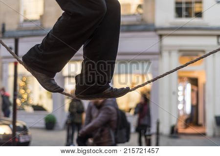 Tight rope walker's legs. Feet of balancing on rope in busy high street with passers by