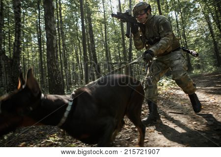 Image of airsoft player with doberman and submachine gun in forest on reconnaissance poster