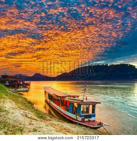 Touristic boat at sunset time. Beautiful landscape. Luang Prabang. Laos.