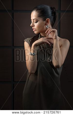 Back view of attractive brunette girl with closed eyes long eyelashes makeup plump lips touching neck and chin. Beautiful woman with big rounded earring shiny manicure.