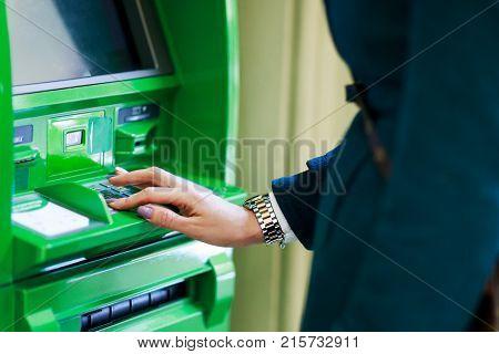 Image of girl picking pincode at green cash dispenser in room