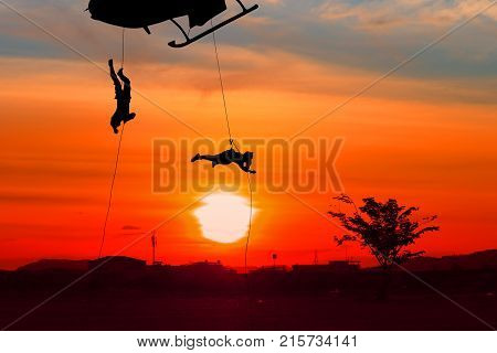 Silhouette Soldiers rappel down to attack from helicopter in blue sky with blur propeller