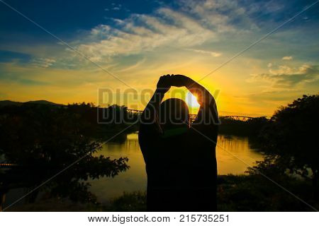 Silhouette of man obese exercise and yoga practicing in sunrise the morning with copy space add text