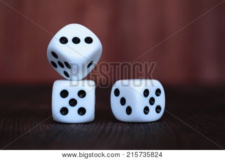 Pile of three white plastic dices on brown wooden board background. Six sides cube with black dots. Numbers 1 3 and 5.
