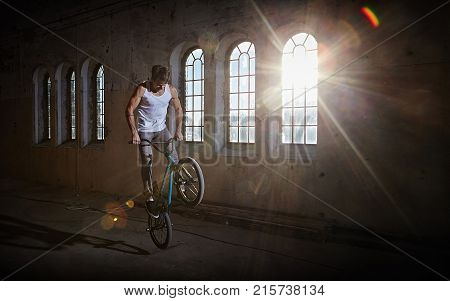 BMX stunt and jump riding in a sunlight, indoor park.