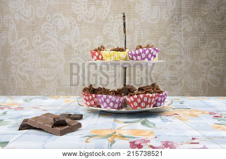 Homemade chocolate cakes on a cake stand with pieces of chocolate