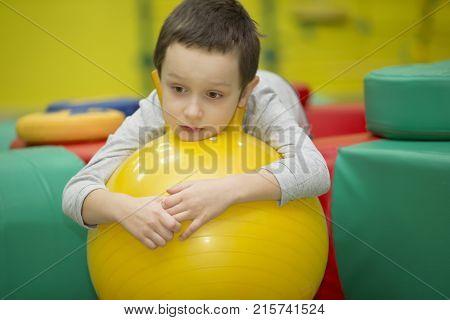 Belarus Gomel November 9 2017. Gomel Children's Center. Children's holiday.Sad child in the gym.Boy on a rubber gymnastic ball
