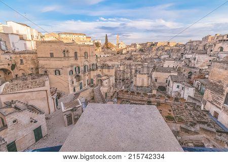 panoramic view of typical stones (Sassi di Matera) and church of Matera under blue sky. Basilicata Italy
