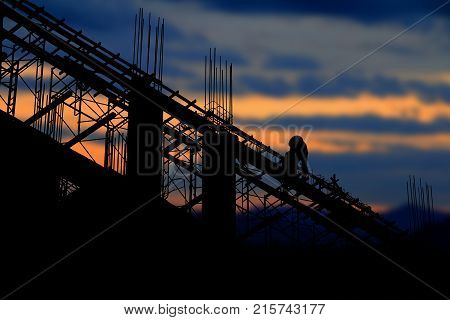 silhouette of worker on Concrete purlin construction on industry site at concept sunrise time background with copy space add text
