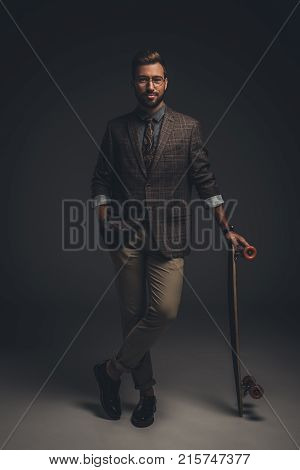Man In Suit Posing With Skateboard