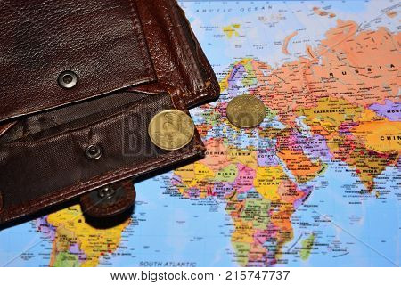open wallet with two euro cents lies on the world map the concept of poverty