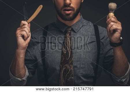 Man Holding Razor And Shaving Brush