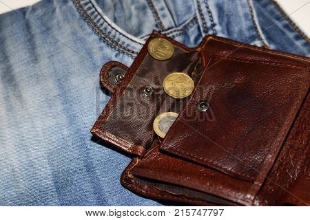 An open wallet with two euro cents is on jeans the concept of poverty
