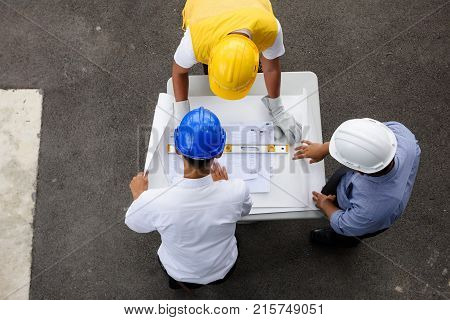 Top view of engineering team of site manager field engineer and foreman looking at constructed paper blueprint plans at construction site. Business Concept for team work of heavy industry.