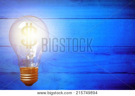 Light bulb with Dollar symbol on blue wooden background. Money making idea concept