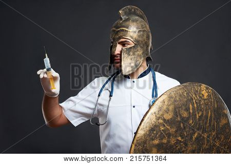 Horizontal shot of medical warrior in a helmet posing with a syringe and a shield against dark background protector warrior soldier safety preventive treatment vaccination medicine healthcare concept.