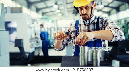 Male worker and quality control inspection in metal industry factory