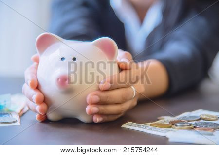 Piggy bank in hand with cash pile on wooden top table money savings concept.