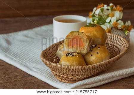 Delicious Chinese pastry or moon cake filled with mung bean paste and salted egg yolk on wood basket. Chinese pastry served with tea on wood table in side view with copy space. Homemade bakery concept of moon cake or Chinese pastry.