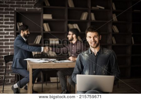 creative sales Manager with notebook on background of business partners handshaking in a modern office