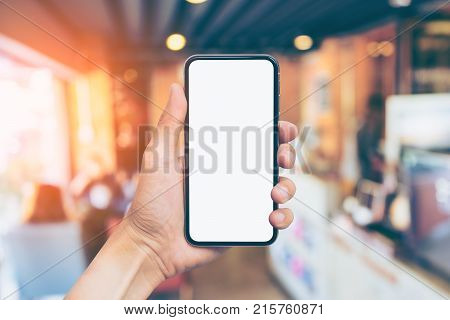 Man's hand shows mobile smartphone with white screen in vertical position Blurred or Defocus image of Coffee Shop or Cafeteria for use as Background vintage tone. - mockup template and clipping path