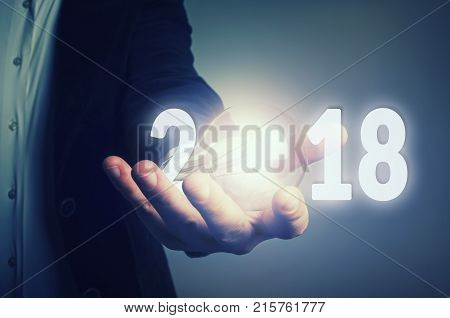 Businessman holding a lightbulb and number 2018 year. Business idea new year concept.