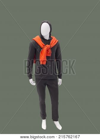 Full-length male mannequin wearing clothes for sport over green background. No brand names or copyright objects.
