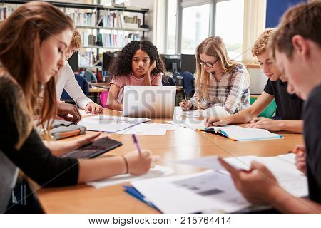 Group Of College Students Working Around Table In Library
