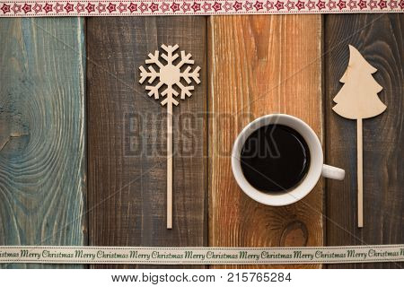 A colored wooden Christmas background with a cup of coffee between a wooden Christmas-tree and snowflake. A star patterned ribbon at the top. A Merry Cristmas inscription ribbon on the bottom. Copy space. Top view