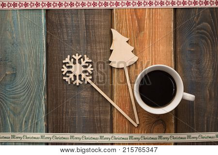 A colored wooden Christmas background with a cup of coffee, wooden Christmas-tree and snowflake. A star patterned ribbon at the top. A Merry Cristmas inscription ribbon on the bottom. Copy space. Top view
