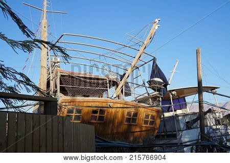 Old wooden yachts stands waiting for renovation in the dock