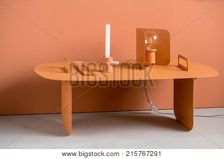 Steel orange table on the same wall background indoors. On the table there is an orange support, metal orange lamp with edison light bulb, orange candlestick with a white candle. Closeup. Horizontal.