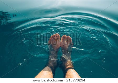 Male feet in outdoor swimming pool. Man enjoying refreshing poolside water in summer sunset. Holidays vacations and weekend activities.