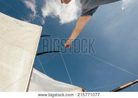 Professional sailor or yachtsman uses mast and forestay to put up spinnaker or mainsail on racing competition yacht or sailboat on warm summer day. Points on sail in blue sky